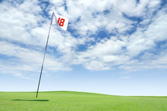 Golf flag at hole 18 on the putting green. Putting green with a flag marking the 18th hole on a golf course stock image