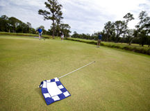 Golf flag and players Stock Photography