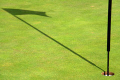 Golf flag shadow. Close up of flag casting shadow on a green golf field Royalty Free Stock Photos