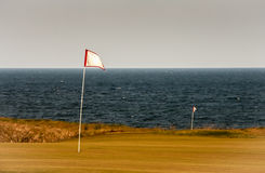 Golf Flag. Waves in the wind with the ocean behind it Stock Images