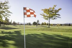 Golf Flag Waving. With the sun shining from behind Stock Images