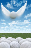 Golf Flight 2A. Illustration of an amazing golf ball with wings flying up into sky above crowded, regular golf balls on the ground Royalty Free Stock Photo