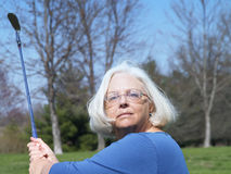 Golf grandmother. A senior woman practicing her golf swinging skills Stock Photo