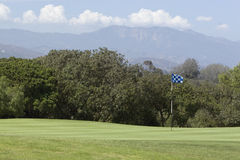 Golf Green. With blue and white checked pin flag. Mountains and fluffy white clouds in background stock photo
