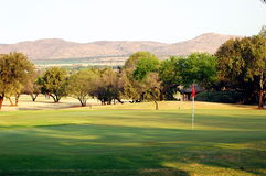 Golf green. A view of a green, with the veldt and a dam in the background Royalty Free Stock Images