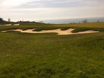 Golf green with bunkers in afternoon sunlight. Panoramic view of golf green with white sand traps. Golf course flyover. Golf green with bunkers in afternoon Stock Photography