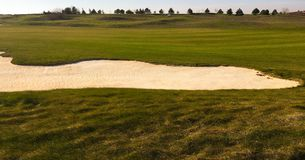 Golf green with bunkers in afternoon sunlight. Panoramic view of golf green with white sand traps. Golf course flyover. Golf green with bunkers in afternoon Stock Images