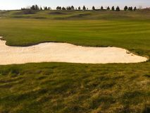 Golf green with bunkers in afternoon sunlight. Panoramic view of golf green with white sand traps. Golf course flyover. Golf green with bunkers in afternoon Royalty Free Stock Image