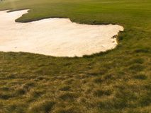 Golf green with bunkers in afternoon sunlight. Panoramic view of golf green with white sand traps. Golf course flyover. Golf green with bunkers in afternoon Royalty Free Stock Images