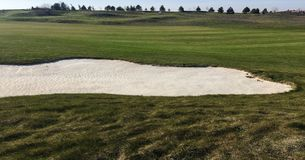 Golf green with bunkers in afternoon sunlight. Panoramic view of golf green with white sand traps. Golf course flyover. Golf green with bunkers in afternoon Royalty Free Stock Photo