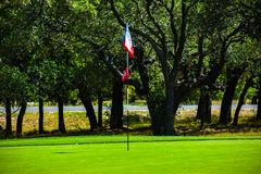 Golf Green in Central Texas lined with Trees with a lonestar Texas flag as golf flag. Golf Green in Central Texas lined with Trees, Fairway under a bright blue royalty free stock photos