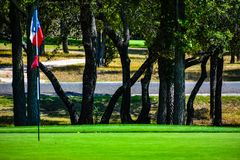 Golf Green in Central Texas lined with Trees with a lonestar Texas flag as golf flag. Golf Green in Central Texas lined with Trees, Fairway under a bright blue royalty free stock photography