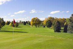 Golf Green And Flag. Nice early fall day on the golf course green. Colorful and cool. A great day to play Royalty Free Stock Images