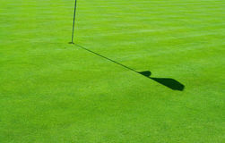 Golf green and a flag shadow. A hole with a flag pole and a shadow on a perfect green grass Stock Photo