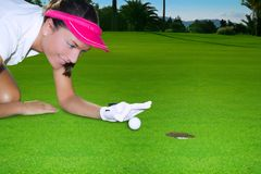 Golf green hole woman humor flicking hand a ball. Golf green hole course woman humor flicking hand a ball inside in short putt Stock Images