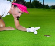 Golf green hole woman humor flicking hand a ball. Golf green hole course woman humor flicking hand a ball inside in short putt Royalty Free Stock Image