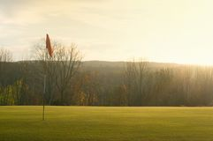 Golf Green and Pin in the Autumn Mountains Shot Against the Sun. Horizontal stock photos