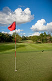 Golf green with red waving flag Stock Photo