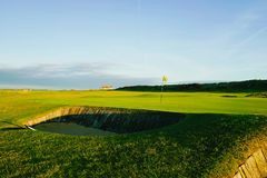 Golf green and flag. Golf green with yellow flag on black and white pole with a bunker at the e Royalty Free Stock Photo