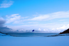 Golf green with winter snow and blue flag. A snow covered links golf hole in ireland in winter evening weather with blue flag Stock Photos