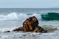 Golf het breken achter rots dichtbij Vreedzame kust; schuim in voorgrond, hemel op achtergrond royalty-vrije stock afbeeldingen