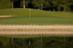 Golf hole. Over water hazard early in the morning with some dew on the green. Focus on flag and reflection Stock Images