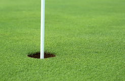 Golf hole. With pole sticking out stock image