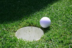Golf hole. Golf ball just next to the hole Stock Images