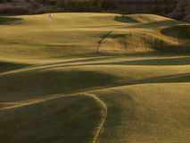 Golf hole. In desert at sundown Royalty Free Stock Photography