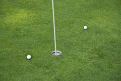Golf hole. On a green with two balls Stock Photography
