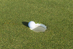 Golf hole and ball on a field Royalty Free Stock Photo