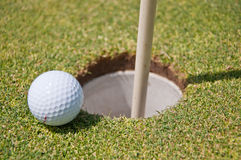 Golf hole with ball and flag stock photo