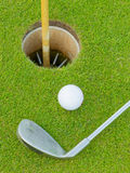 Golf hole with ball and putt Royalty Free Stock Photos
