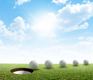 Golf Hole And Ball Putt Path. A perfectly manicured golf putting green showing a ball in motion on its way to the hole in the daytime on a blue sky background Royalty Free Stock Images