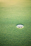 Golf hole. Closeup of golf hole on putting green in the evening light Royalty Free Stock Images