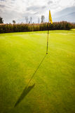 Golf hole at dawn. A golf hole with a flag pole in a beautiful golf course Royalty Free Stock Photo