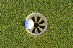 Golf hole on a field and golf ball Stock Photo
