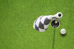 Golf hole flag on a field. Golf ball and hole flag on a field Royalty Free Stock Images