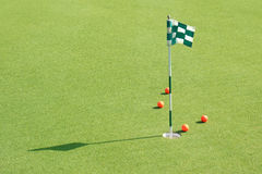 The golf hole with flag and golf balls on green grass of golf co. Urse Stock Photo