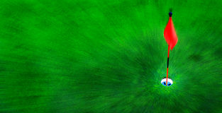 Golf Hole on Green Grass with Red Flag. Red flag and hole for golf on green grass Royalty Free Stock Image