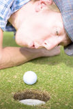 Golf Hole In One Puff. Desperately Wanting Hole In One Off Four Par, Golfer Puffs On Golf Ball To Motion It Into The Hole In Funny Golfing Cheat Concept Royalty Free Stock Photography