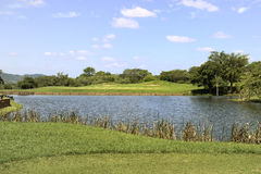 Golf Hole Panorama. Golf hole panoramic view from the tee to the green with water hazard Royalty Free Stock Images