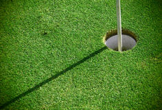 A golf hole and a pin. Golf green detail with a hole and a pin Stock Photography