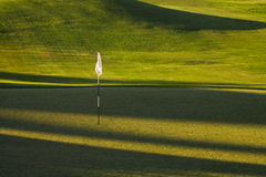 Golf hole shadows. Golf hole and flag late afternoon Royalty Free Stock Photo