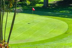 Golf Course Hole Overlooking Green Flagstick. Golf course hole overlooking putting green Flag-stick trees scenic summer coastal course stock image