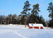 Golf house and winter green. A red house on a snow covered golf course with ski tracks Stock Photos