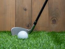 Golf i piłka na tle zielonej trawy i drewna Zdjęcie Royalty Free