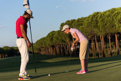 Golf instructions. Male golf instructor teaching female golf player, personal trainer giving lesson on golf course Royalty Free Stock Photography