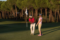 Golf instructions. Male golf instructor teaching female golf player, personal trainer giving lesson on golf course Stock Photos