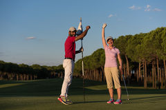 Golf instructions. Male golf instructor teaching female golf player, personal trainer giving lesson on golf course Stock Image